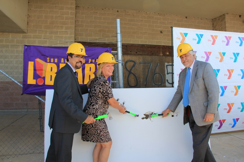 (From left) San Antonio Public Library Director Ramiro Salazar, YMCA President and CEO, Sandy Morander and Councilman Ray Lopez (D6) participate in a wall breaking ceremony for the Mays Family YMCA at Potranco. Photo courtesy of YMCA of Greater San Antonio.