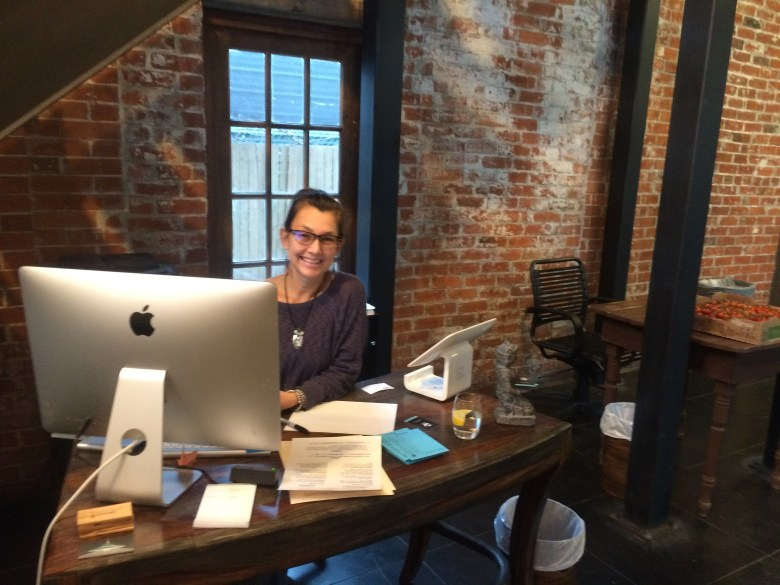 After greeting customers, Lisa Asvestas, owner of 5 Points Local, works at her desk on the opening day of the restaurant. Photo by Camille Garcia.