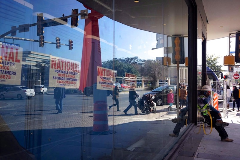 A construction worker makes a phone call outside the Joske's Building. Portable toilets sit beyond the soon-to-be display window for H&M. Photo by Iris Dimmick.