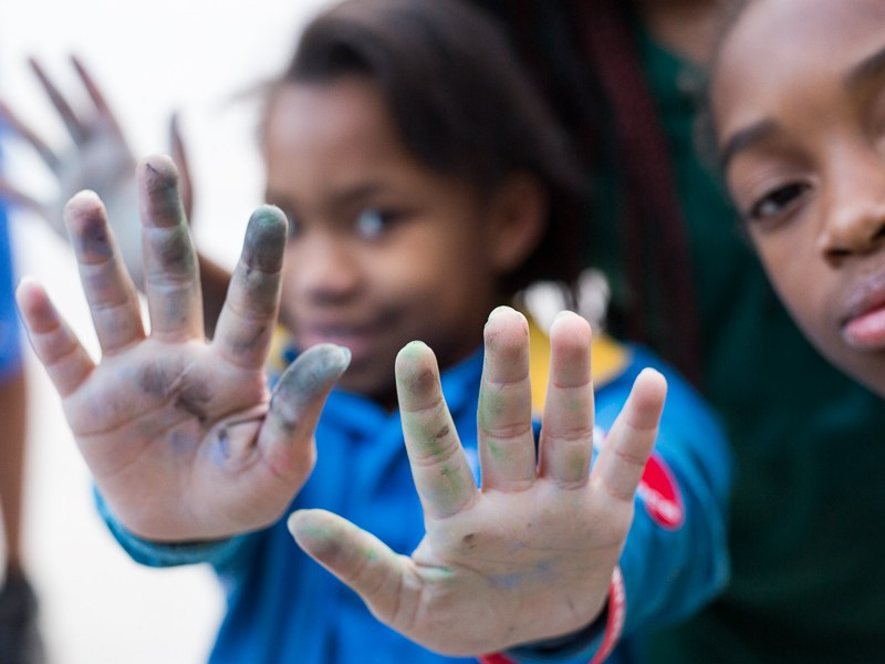 Kids show off their hands which have been covered with multiple colors of chalk. Photo by Scott Ball.
