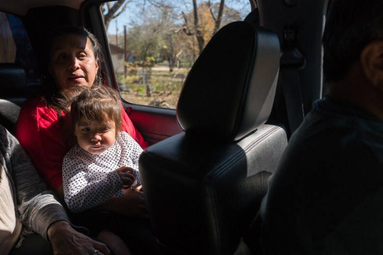 Highland Oaks resident Maria Bernal holds her daughter as they take a ride through their neighborhood. Photo by Scott Ball.