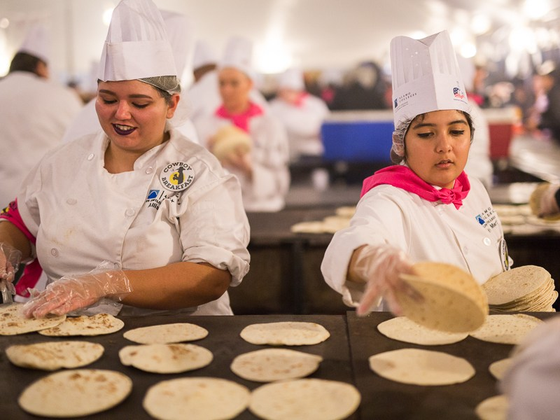 St. Phillips Colleger culinary students Allison Fox (left) and Yasmine Martinez prepare tortillas for breakfast tacos. Photo by Scott Ball.