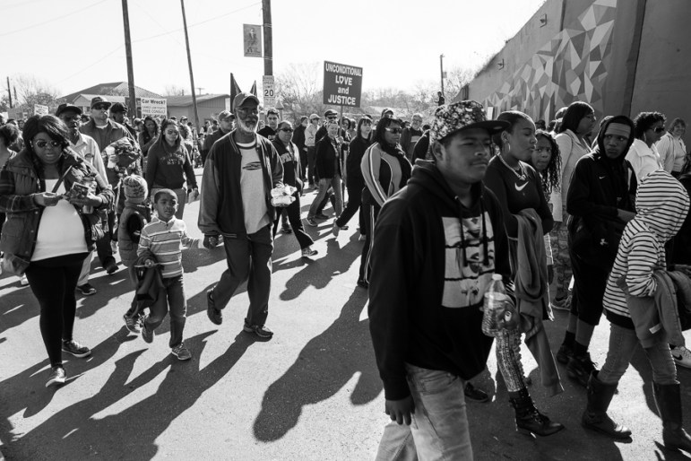 March attendees walk down Martin Luther King Drive as they pass a newly constructed mural. Photo by Scott Ball.