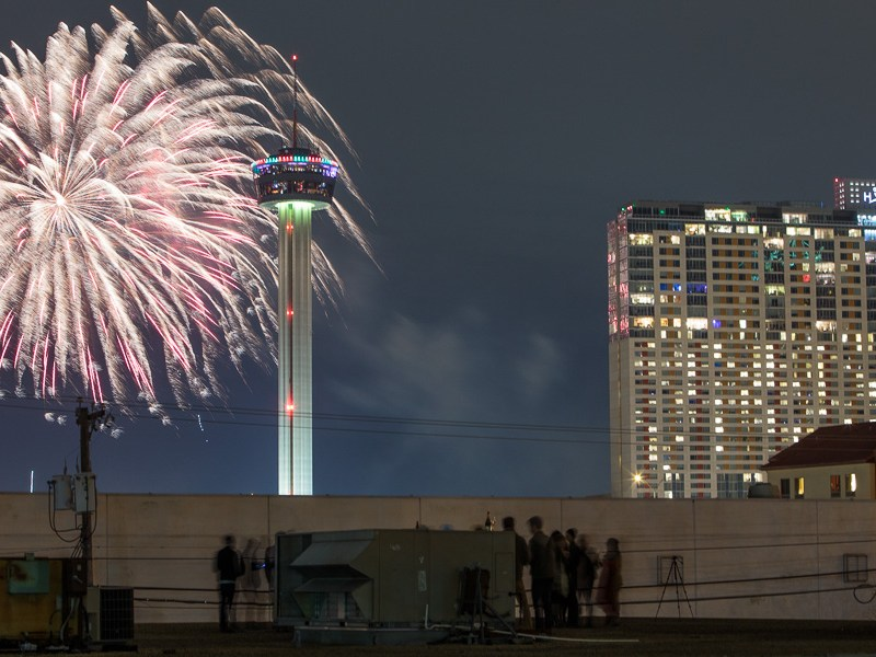 Friends are gathered on a rooftop watching the downtown fireworks show. Photo by Scott Ball.