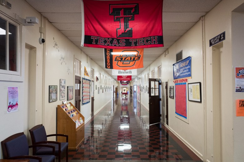 Flags of colleges are hung from the ceilings of YWLA. Photo by Scott Ball.