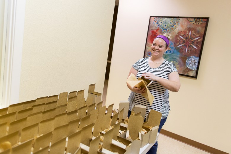 Becca Brem adds tissue paper to gift boxes. Photo by Rachel Chaney.