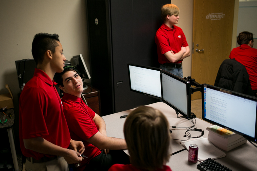 Kyle Volz works with Hector Iruegas on finding cybersecurity vulnerabilities in an online operating system. Photo by Kathryn Boyd-Batstone