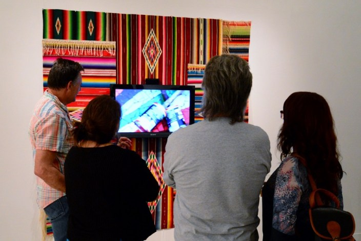 Participants view a work by Jimmy James Canales at CAM Perennial 2015. Photo by Page Graham.