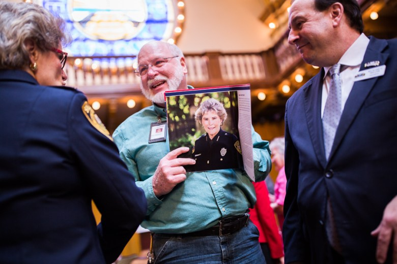 Attendee Gary Carpenter (center) points out Sheriff Susan Pamerleau's achievements while holding an informational booklet displaying her portrait. Photo by Scott Ball.