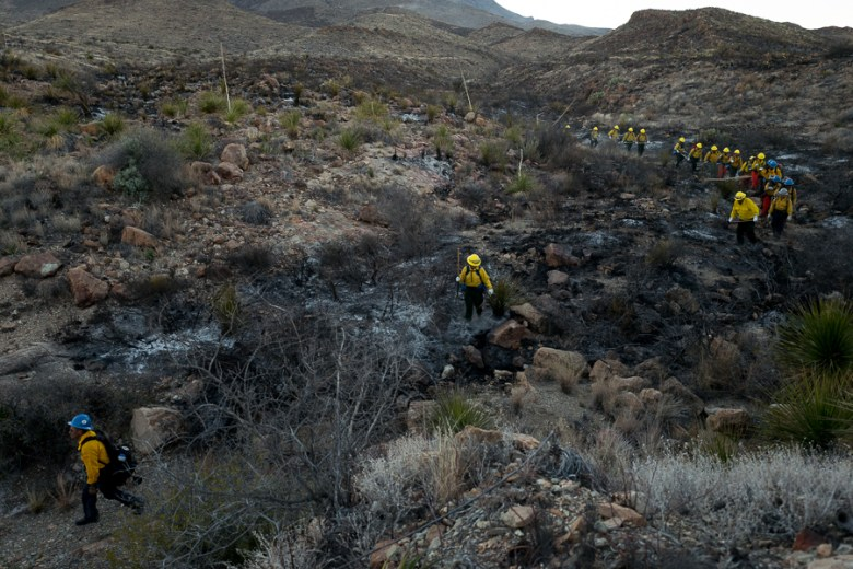 A line of firefighters from the New Mexico based Zuni Hotshots work their way down a burnt creek bed to navigate back to a main road. Photo by Scott Ball.