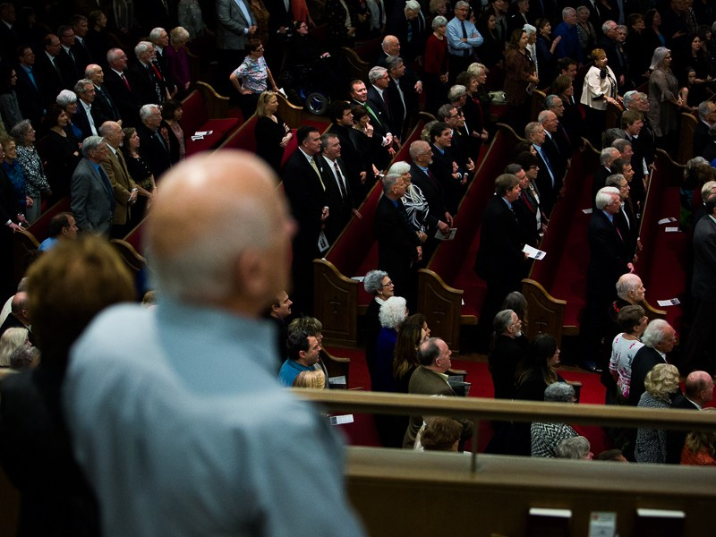 Guests stand during the singing of a hymn opening the memorial for Buckner Fanning. Photo by Scott Ball.