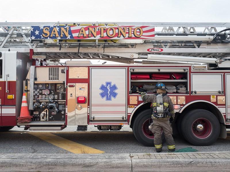 A firefighter organizes equipment in a ladder truck. Photo by Scott Ball.
