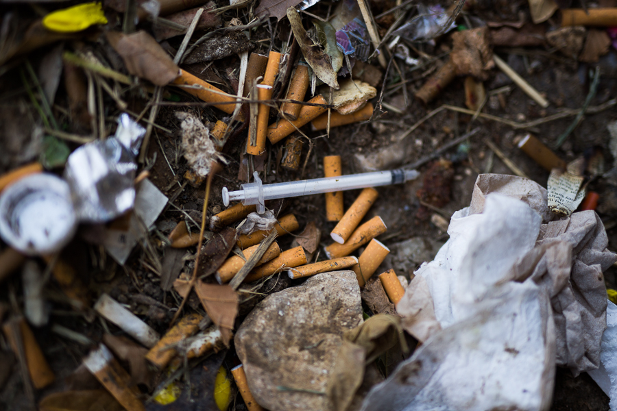 A hypodermic needle lays on the ground near a cleanup site. Photo by Scott Ball.