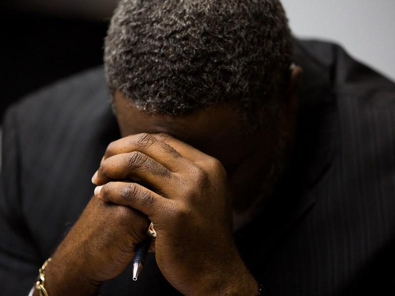 A member of the session bows his head during a prayer. Photo by Scotty Ball.