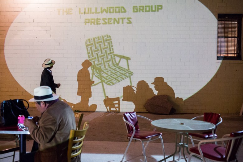 A projection advertising the Lullwood Group is displayed along the brick wall of Gallista Gallery. Photo by Scott Ball.