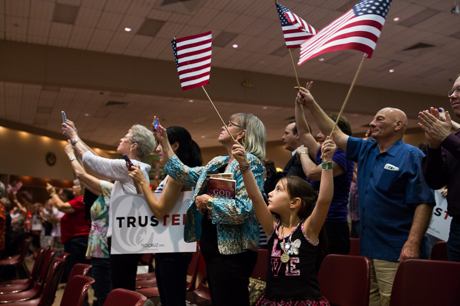 A young girl waves American Flags as Ted Cruz walks on stage. Photo by Scott Ball.