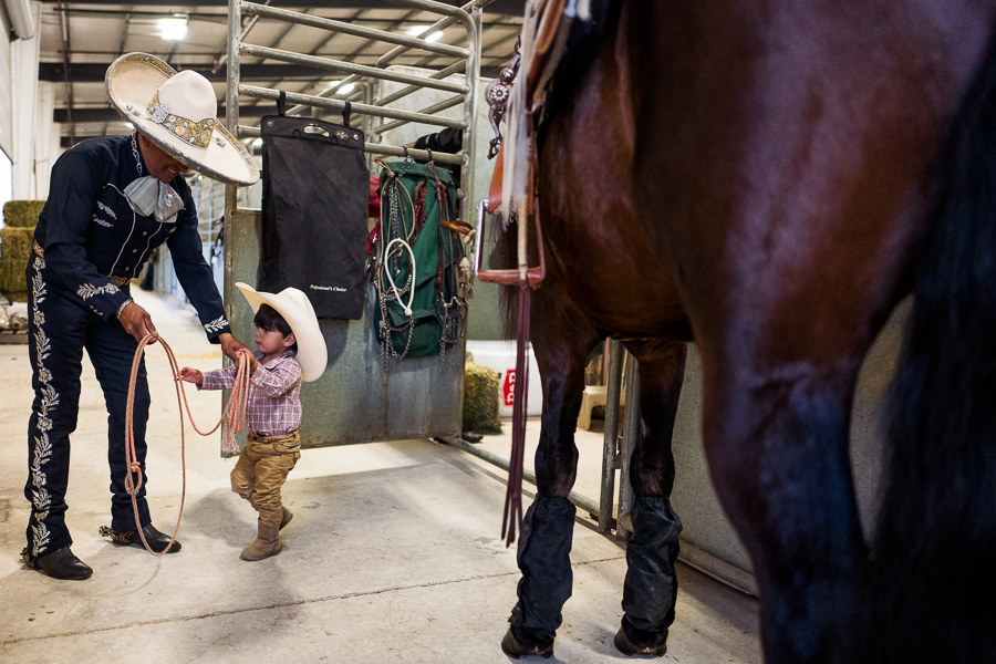 Tomas works with his son Louis, 17 months, on the proper way to hold a rope. Photo by Scott Ball.