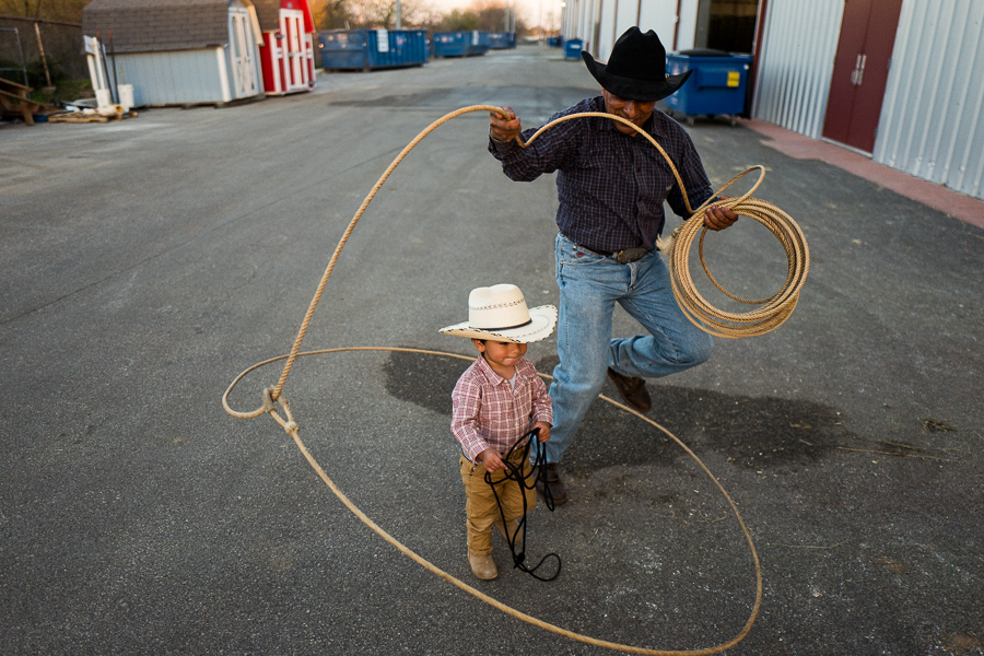 Jesús Garcilazo performs rope tricks around his nephew, Louis, 17 months. Photo by Scotty Ball.