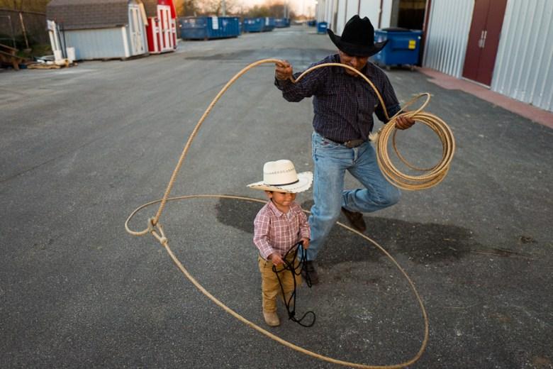 Jesús Garcilazo performs rope tricks around his nephew, Louis, 17 months. Photo by Scott Ball.