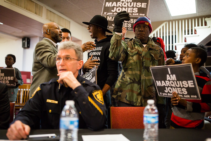 San Antonio Police Chief William McManus sits as protestors, including Mike Lowe, surround him asking for justice for Marquise Jones and Antronie Scott. Photo by Scott Ball.