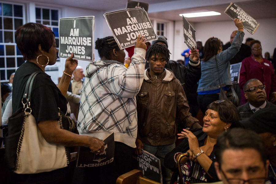Protestors file in-between the pews of New Point Baptist Church. Photo by Scott Ball.