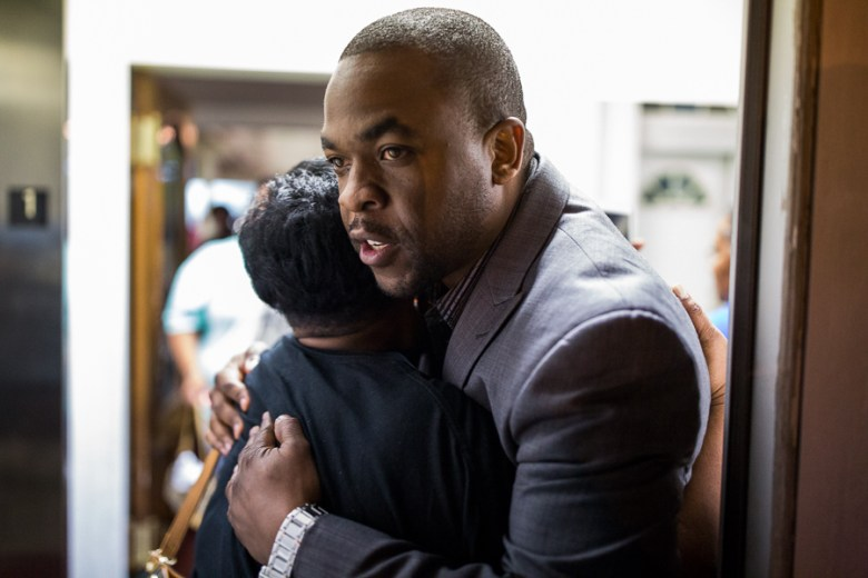 Journalist and civil rights activist Taj Matthews embraces Debby Bush apologizing to her for being cut off during her speech. Photo by Scott Ball.
