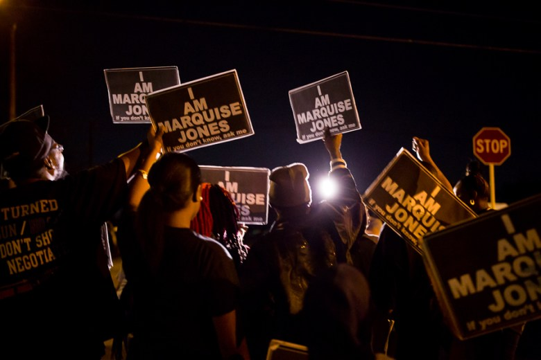 """Protestors raise signs displaying """"I Am Marquise Jones"""" for a television camera. Photo by Scott Ball."""
