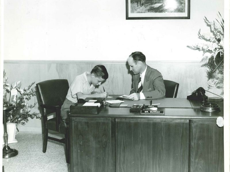 A.J. Lewis, son of Jefferson Bank's founding chairman Jack Lewis, opens the bank's first savings account on opening day, Aug. 12, 1946, with help from bank president, Tom Murrah. Courtesy photo/