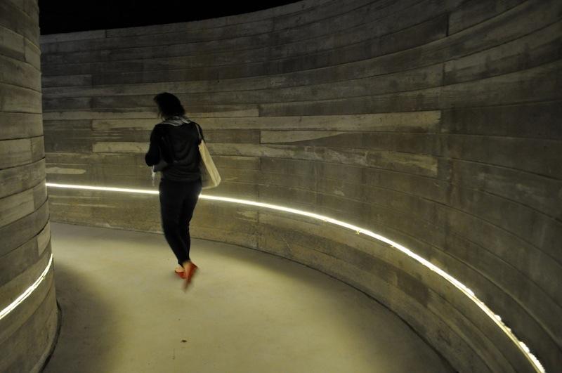 A tour participant walks through the dimly lit entrance to the cistern at Buffalo Bayou, Houston. Photo by Iris Dimmick