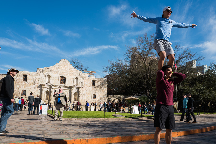 Tourists perform a circus like stunt on Alamo Plaza for a photograph to send to their friends ands family. Photo by Scott Ball.
