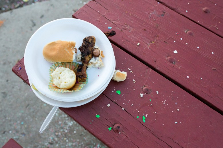 A plate of chicken, hot dog, and half of a cupcake is left on a picnic table at Brackenridge Park. Photo by Scott Ball.