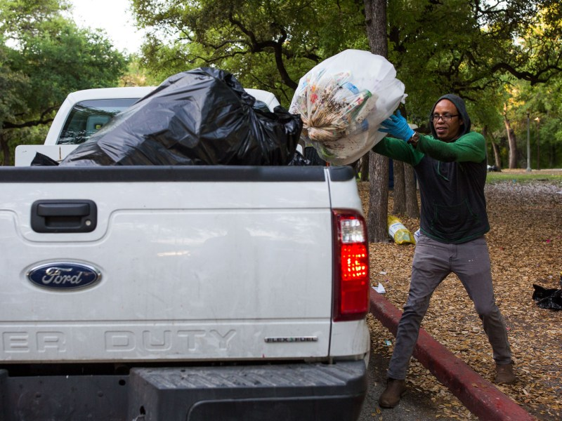 Community service volunteer John County throws another bag of trash on top of others at Brackenridge Park. Photo by Scott Ball.
