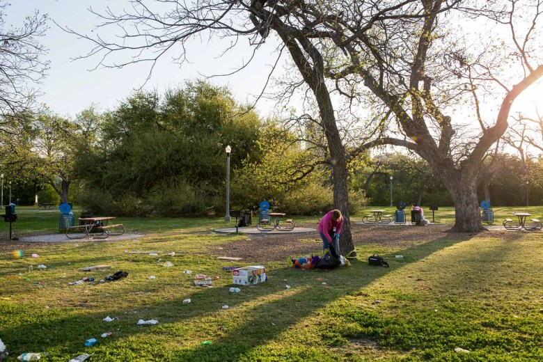 City employee Laura Gomez picks up litter left behind from Easter campers at Brackenridge Park. Photo by Scott Ball.