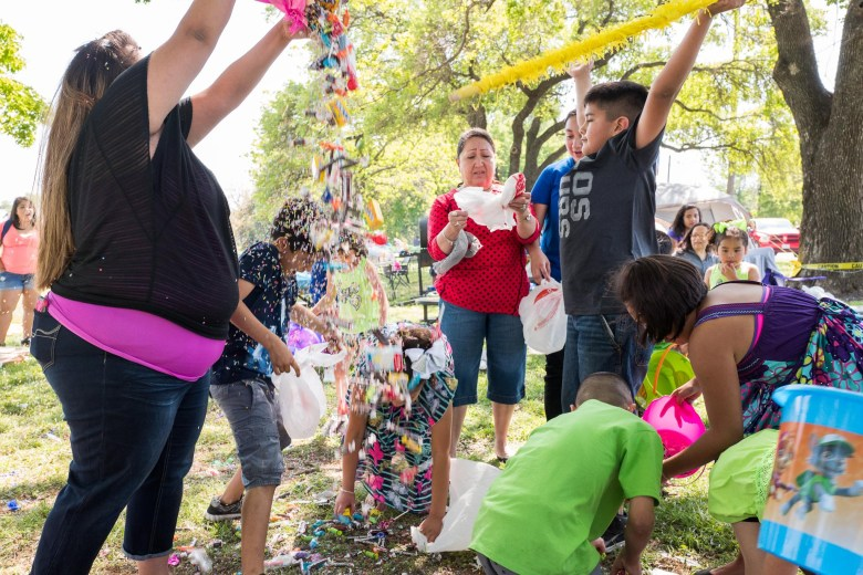 Candy falls from a recently busted piñata as children from the Fernandez family rush to pick up pieces. Photo by Scott Ball.