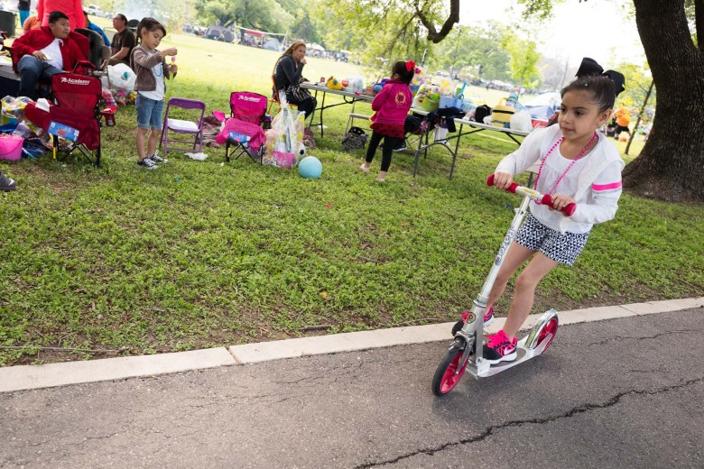 A child pushes her scooter by camping families at Davis Park. Photo by Scott Ball.
