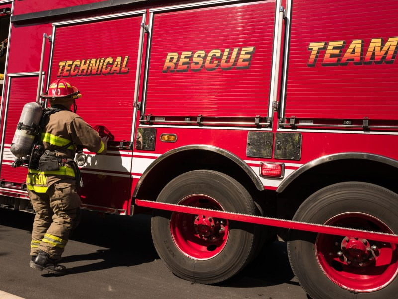 A firefighter retrieves his gear from an engine. Photo by Scott Ball.