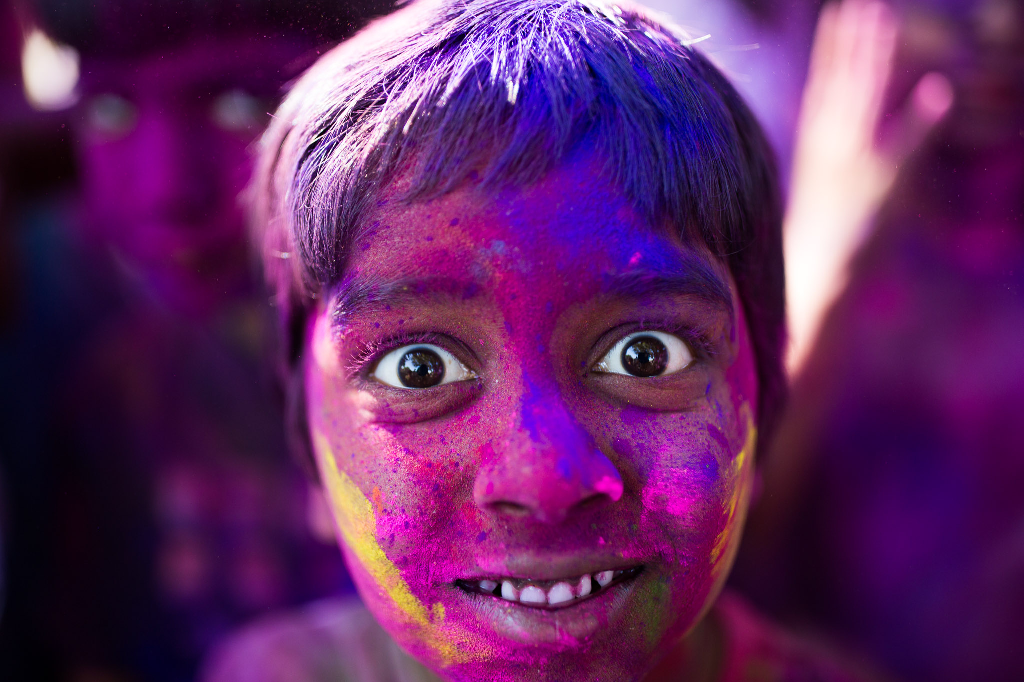 Ritvek, 7 years old, stands in front of the camera after his entire face has been covered with colored powder. Photo by Scott Ball.