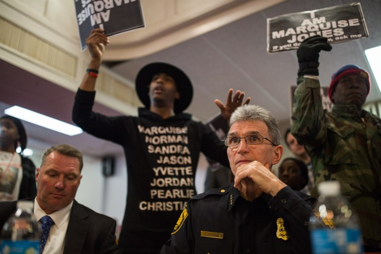 San Antonio Police Chief William McManus sits as protestors including activist Mike Lowe (back left) assemble behind him during a Town Hall at New Light Baptist Church on the Eastside. Photo by Scott Ball.