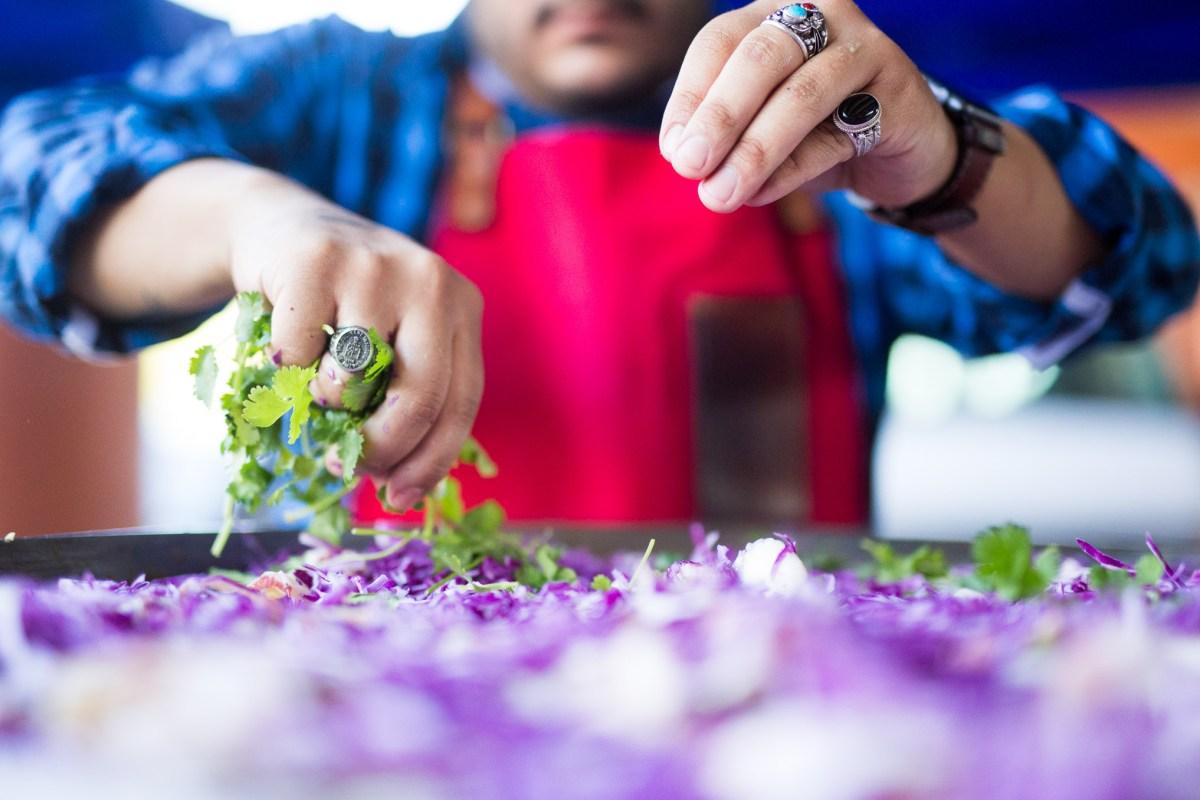 Old Main Association Chef Lorenzo Morales prepares a slaw salad. Photo by Scott Ball.