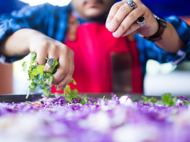 Old Main Association Chef Lorenzo Morales prepares a slaw salad. Photo by Scott Ball.