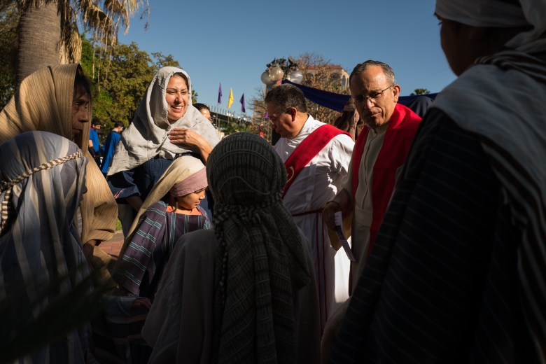 Father David Garcia (right) talks with members of the reenactment. Photo by Scott Ball.