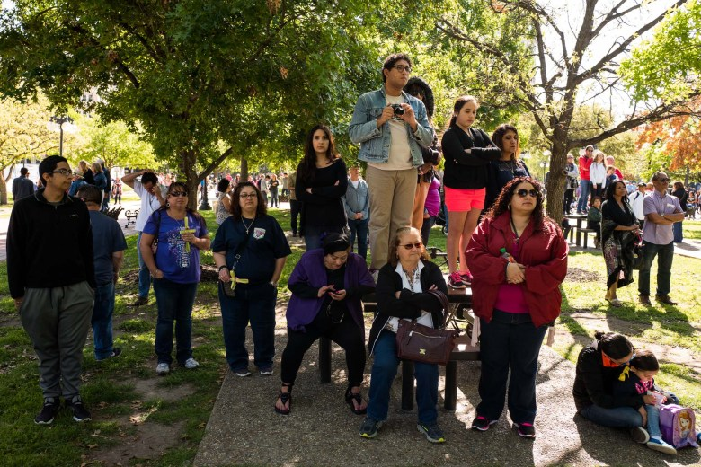 Spectators stand on tables nearby to get a small glimpse of the performance at Milam Park. Photo by Scott Ball.