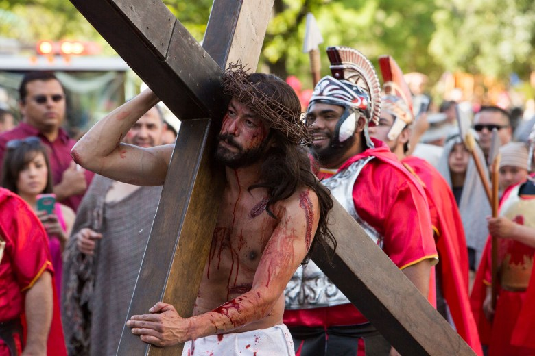 The actor portraying Jesus Christ carries his cross down Houston Street as spectators look on. Photo by Scott Ball.