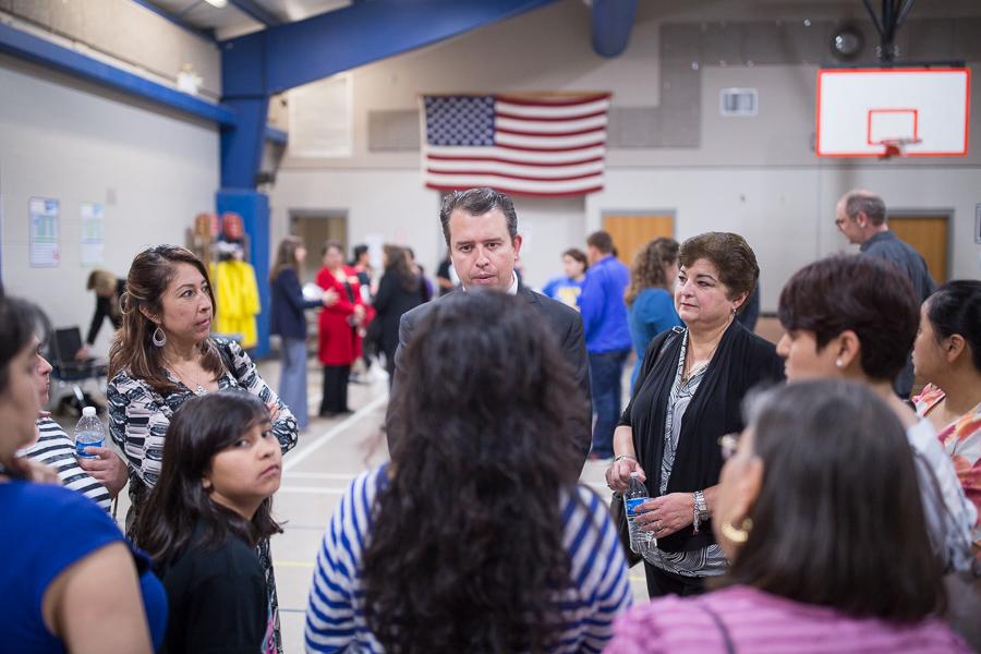 SAISD Superintendent Pedro Marintez and SAISD Board Member Olga Hernandez (D6) is encircled by parents wanting answers. Photo by Scott Ball.