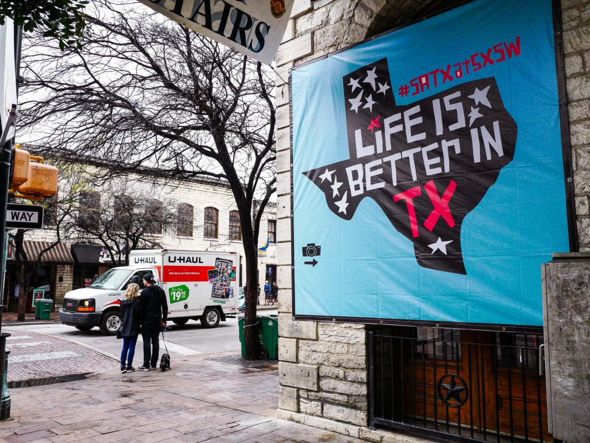A banner hangs on 6th Street advertising the #SATXATSXSW event in Austin Texas. Photo by Scott Ball.