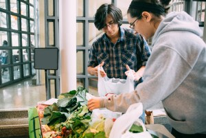 Two Trinity students make preparations for a market sale in the Center for Science and Innovation.