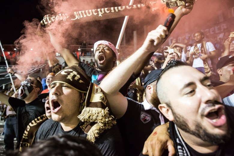A fan waves smoke in the air as he celebrates a San Antonio FC goal. Photo by Michael Cirlos.