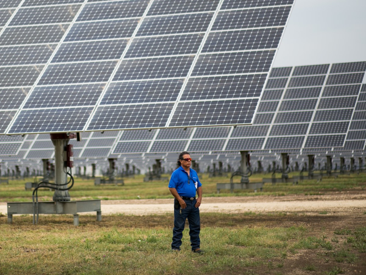 A CPS employee stands before the 378,000-solar-panel installation. Photo by Kathryn Boyd-Batstone