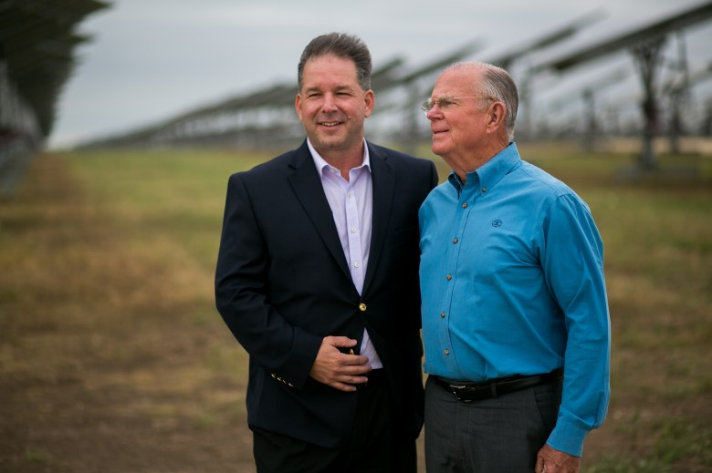 Con Edison Development President and CEO Mark Noyes and former land owner Walter Armstrong stand before the solar power installation. Photo by Kathryn Boyd-Batstone
