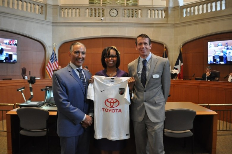 Spurs Sports & Entertainment Vice President of General Counsel and Corporate Relations Bobby Perez (left) and San Antonio FC Managing Director Tim Holt (right) present Mayor Ivy Taylor with a commemorative soccer jersey on Thursday during a City Council meeting in anticipation of the team's first game on Saturday. Photo by Iris Dimmick